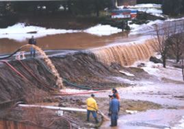People manning a packed earth dam as stormwater drains over and away from it on Lyle Avenue in 1995